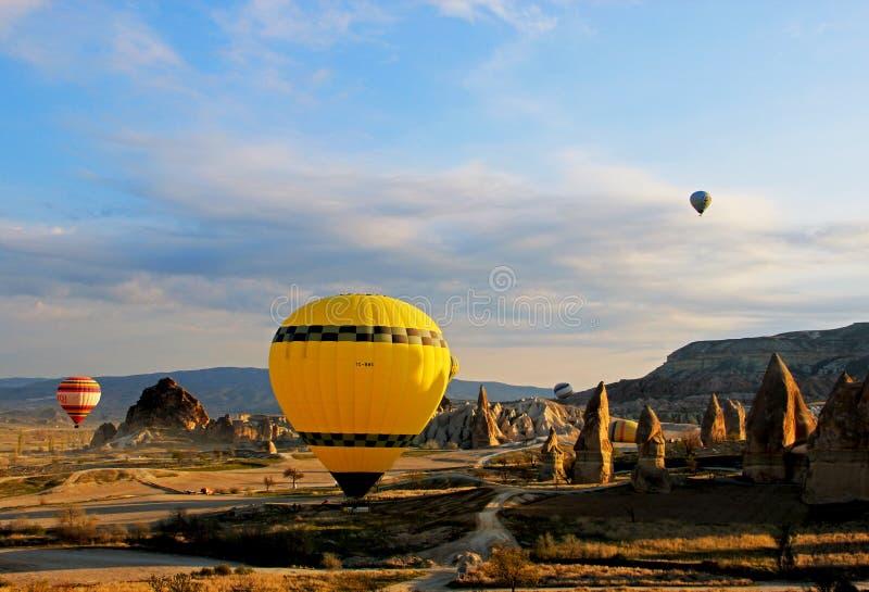 飞行的一个黄色热空气气球在大领域 库存图片