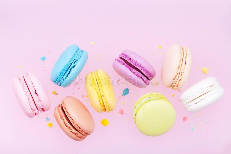 飞行的五颜六色的macaron或蛋白杏仁饼干在桃红色淡色背景 库存照片