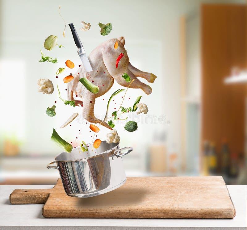 飞行的未加工的鸡汤、肉汤或者汤成份与整鸡,菜,调味料,刀子和烹调罐在厨房 库存照片