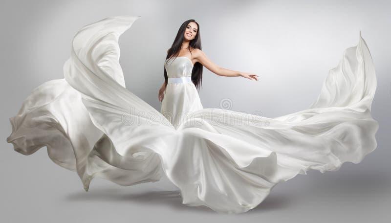 飞行的白色礼服的美丽的女孩 织品流 轻的白色布料飞行 库存图片