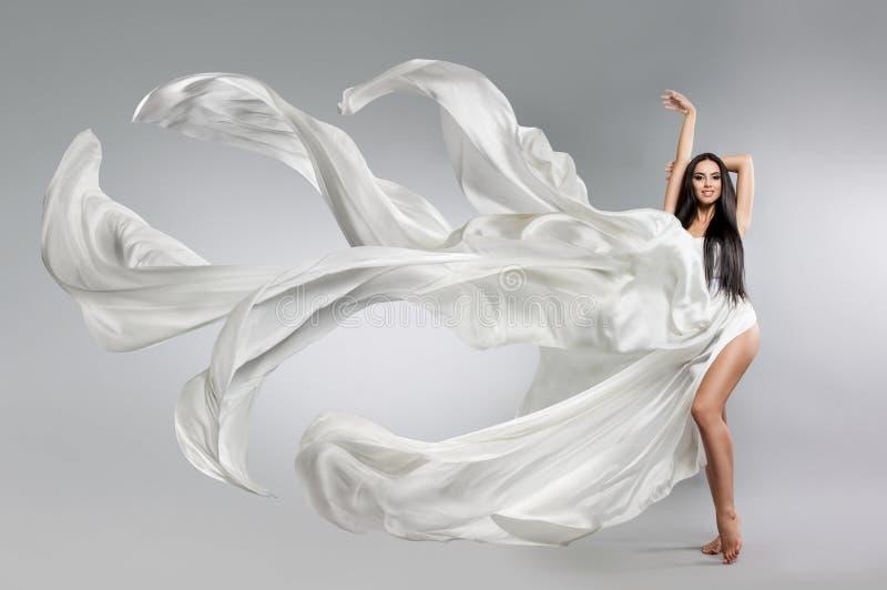飞行的白色礼服的美丽的女孩 织品流 轻的白色布料飞行 免版税库存照片