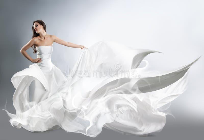 飞行的白色礼服的美丽的女孩 免版税图库摄影
