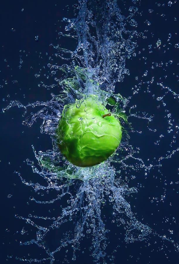 飞行的绿色苹果在水中飞溅 免版税库存图片