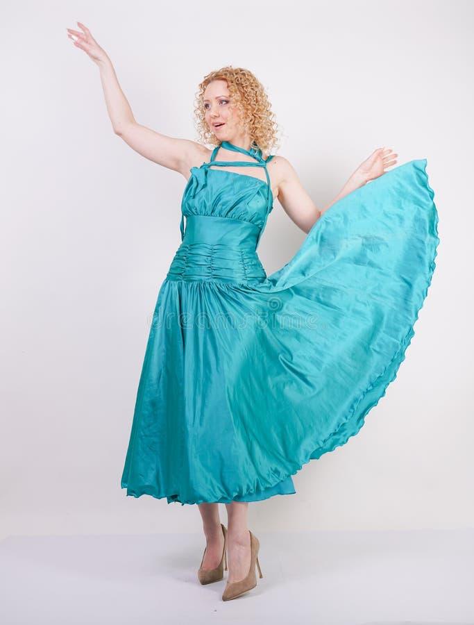 飞行的蓝色晚礼服亭亭玉立的通风女孩在白色背景在演播室 库存照片