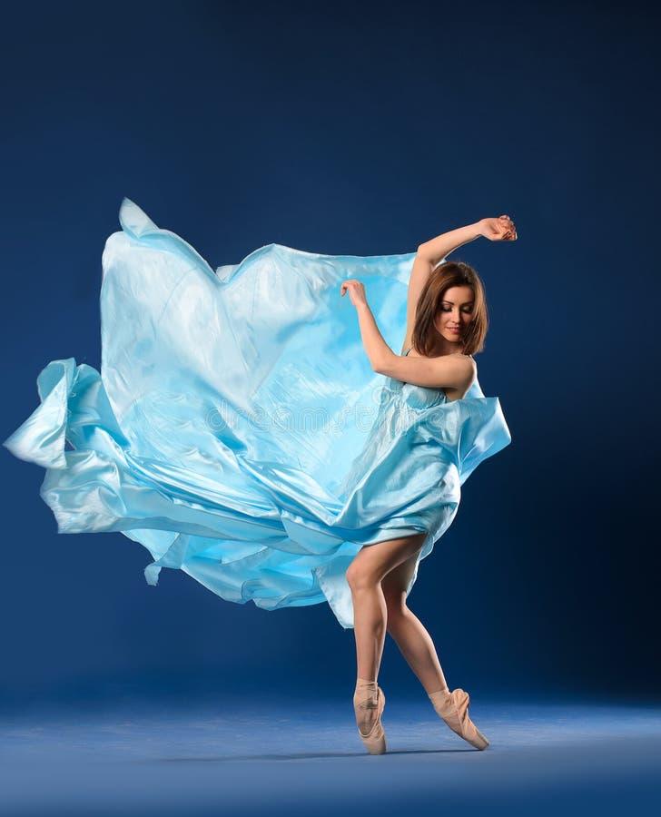 飞行的蓝色礼服芭蕾舞女演员 免版税库存照片