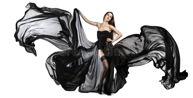 飞行的黑礼服美丽的女孩 织品流 免版税库存图片