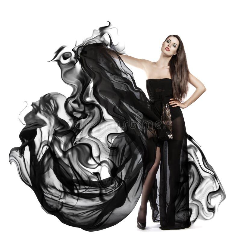 飞行的黑礼服美丽的女孩 织品流 图库摄影