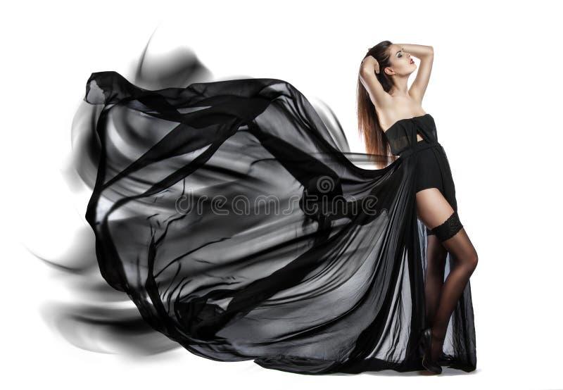 飞行的黑礼服美丽的女孩 织品流 库存照片