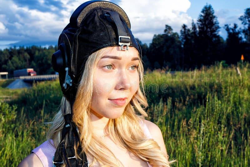 飞行盔甲的女孩飞行员到在绿草背景的夏天之内在晴天 免版税库存图片