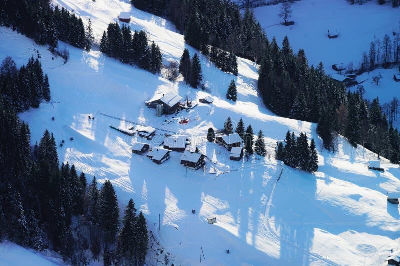 飞行直升机和小村庄伯尔尼高地鸟瞰图  免版税库存照片