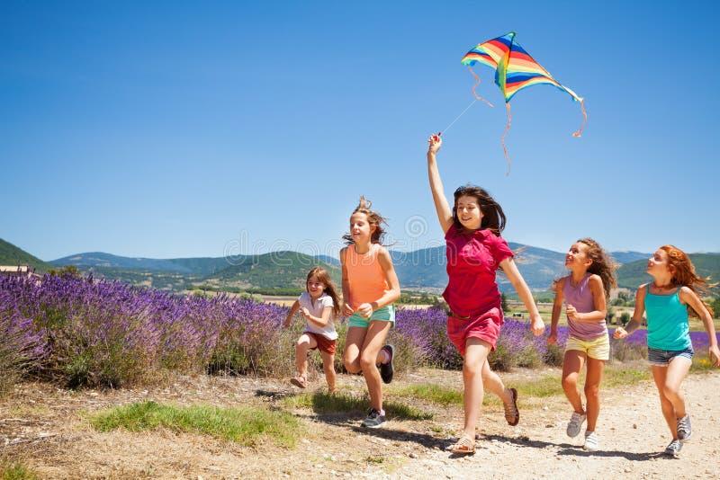 飞行风筝的孩子跑通过淡紫色领域 库存图片