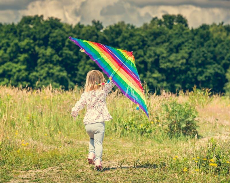 飞行风筝的小逗人喜爱的女孩 免版税库存照片