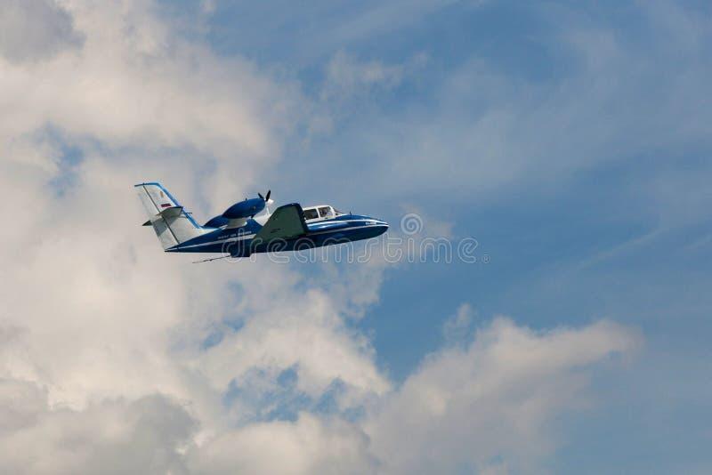 飞行飞机是103在云彩 库存照片