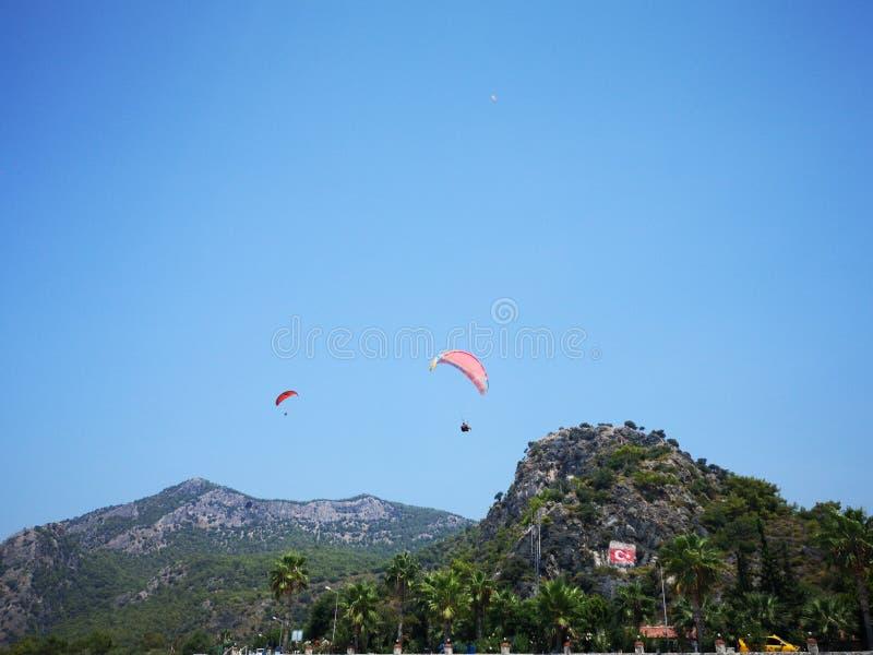 飞行高在夏令时蓝天,费特希耶, Mugla的青山上的一个小组parachuters 图库摄影