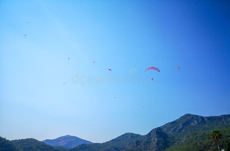 飞行高在夏令时蓝天,费特希耶, Mugla的青山上的一个小组parachuters 免版税库存图片