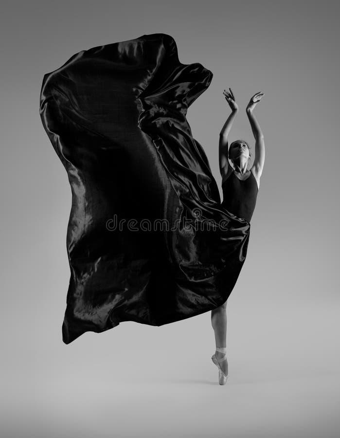 飞行黑色礼服的芭蕾舞女演员 免版税库存图片