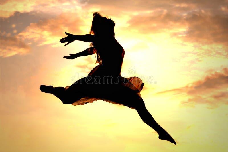 飞跃在日落的妇女 免版税库存图片