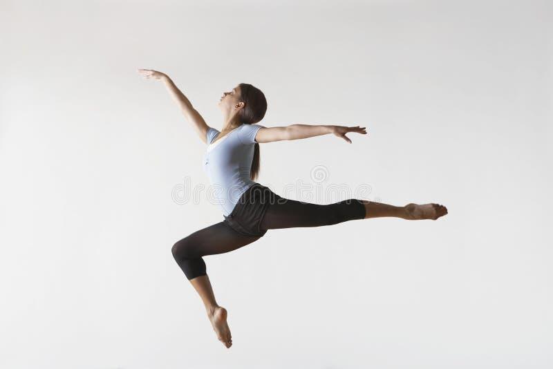 飞跃在空中的女性跳芭蕾舞者 免版税库存照片