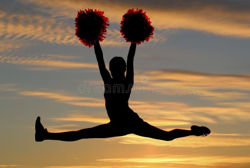 飞跃在空气的啦啦队员剪影做与su的分裂 免版税库存照片