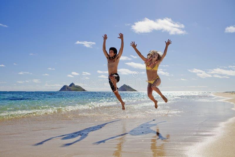 飞跃年轻人的夫妇喜悦 免版税库存照片