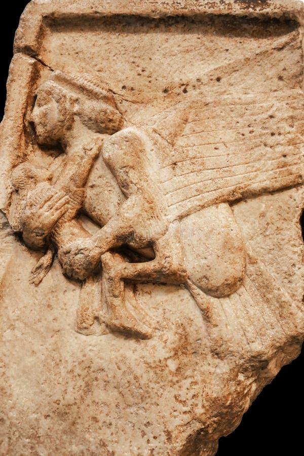 飞过的cherubim或狮身人面象运载的儿童古老雕刻在从老废墟的盘区与镇压和看起来粒状的挖坑的表面 免版税库存照片