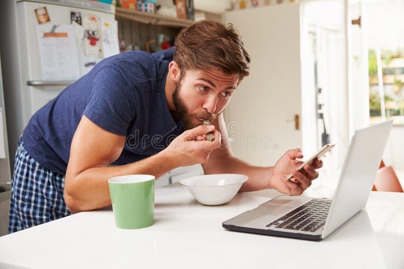食人的早餐,使用手机和膝上型计算机 库存照片
