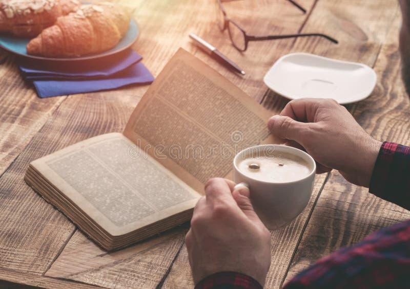 食人的法国早餐和阅读书 免版税库存照片