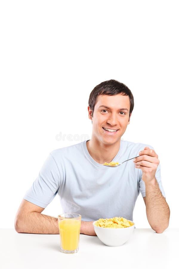 年轻食人的谷物和饮用的橙汁 库存照片