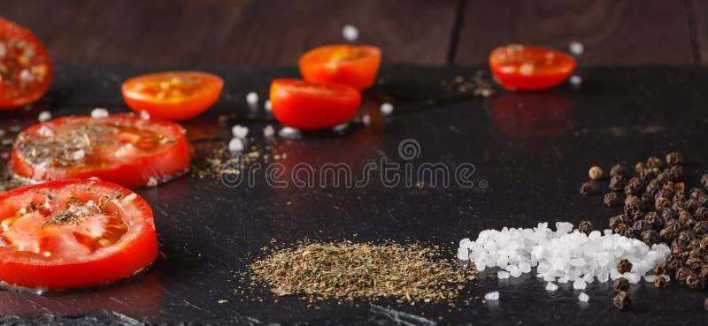 食品成分:蕃茄,在黑板岩石头的盐 库存图片