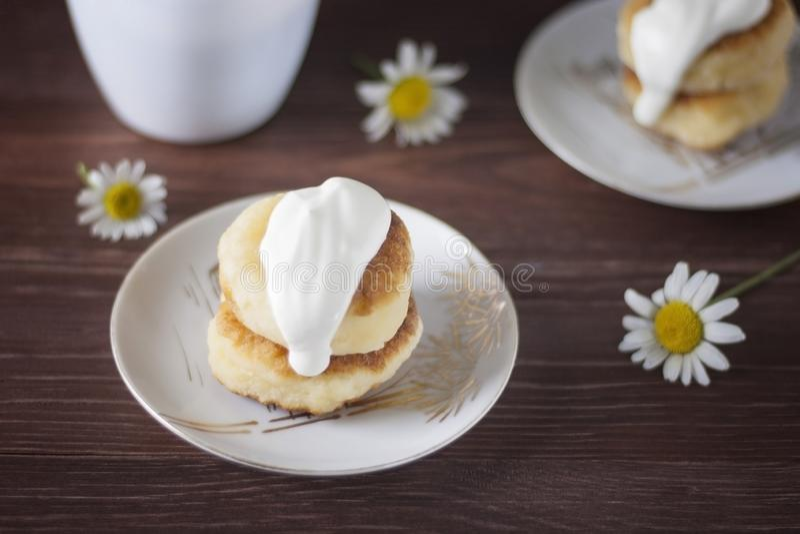 食家早餐-从酸奶干酪的自创酥皮点心,乳酪蛋糕,与酸性稀奶油的酸奶干酪薄煎饼在一块白色板材 免版税库存照片