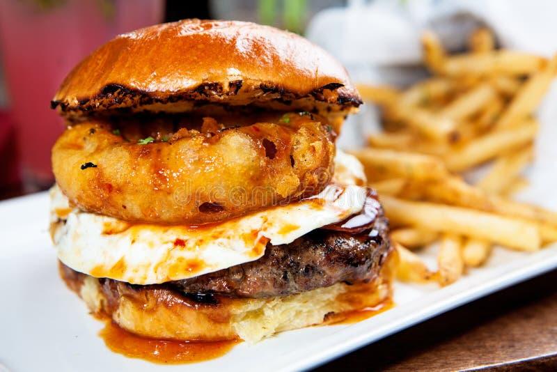 食家汉堡用煎蛋和洋葱圈 库存图片