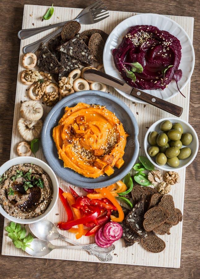 素食快餐桌 南瓜、甜菜hummus、豆和蘑菇头脑,菜,坚果,在一张木桌上的面包,顶视图 库存图片