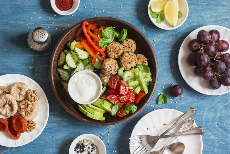 素食快餐桌-奎奴亚藜丸子,新鲜的未加工的蔬菜,葡萄,烘干了在木桌,顶视图上的果子 免版税库存照片
