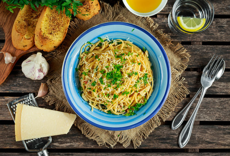 素食意大利面团意粉Aglio E什锦菜用蒜味面包、红色辣椒剥落、荷兰芹、帕尔马干酪和glas  库存图片