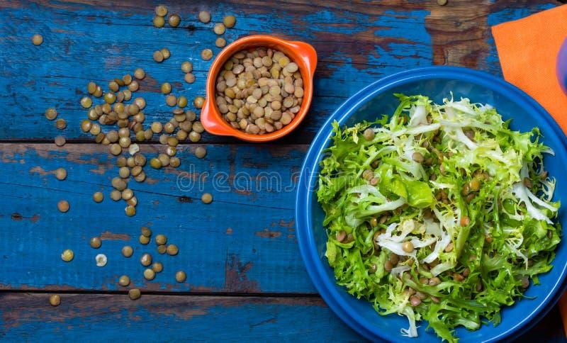 素食沙拉用莴苣和扁豆 五颜六色的蓝色橙色背景 库存图片