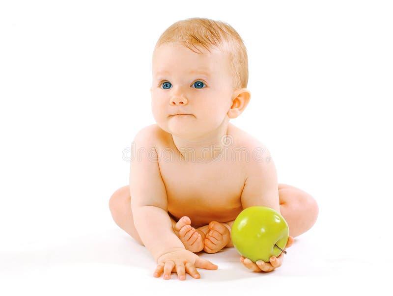 食物、健康和儿童概念 逗人喜爱的婴孩用在a的绿色苹果 免版税图库摄影