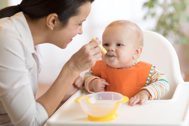 食物、孩子和父母身分概念-妈妈用纯汁浓汤和匙子哺养的婴孩在家 免版税库存图片