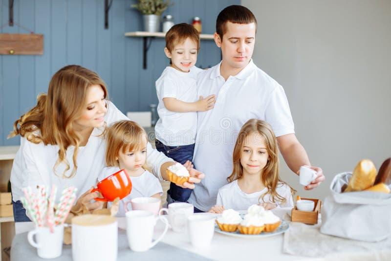食物、家庭、孩子、幸福和人概念-与三个孩子的愉快的家庭在厨房里 免版税库存图片