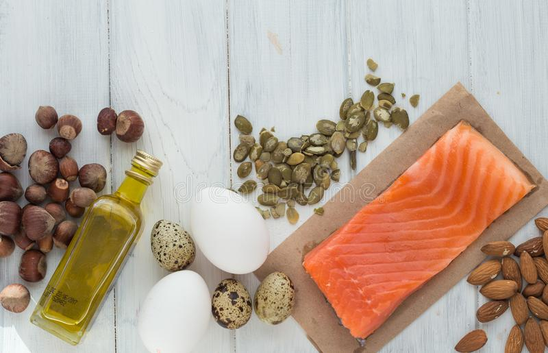 食物健康有机 与健康油脂的产品 Ω 3 Ω 6 成份和产品:鳟鱼三文鱼橄榄油鲕梨坚果 免版税库存图片