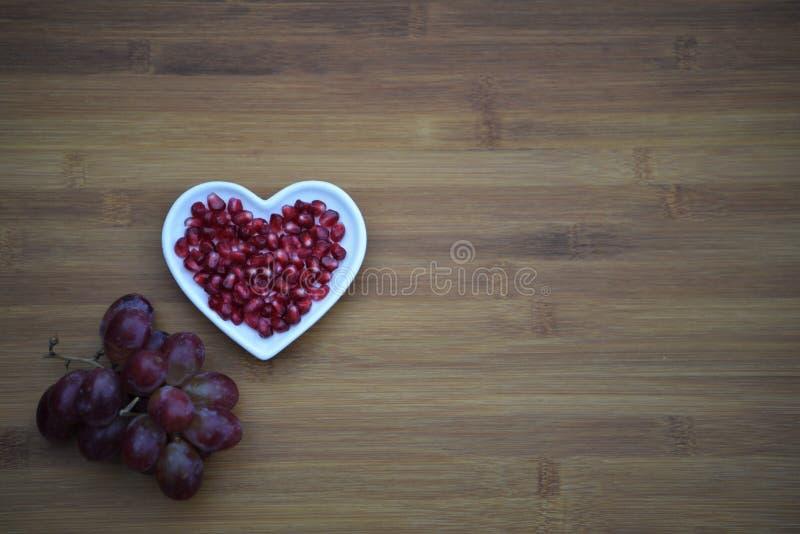 食物健康红色石榴种子的摄影图象在一个白色爱心脏形状盘的用在木背景的紫色葡萄 免版税库存照片