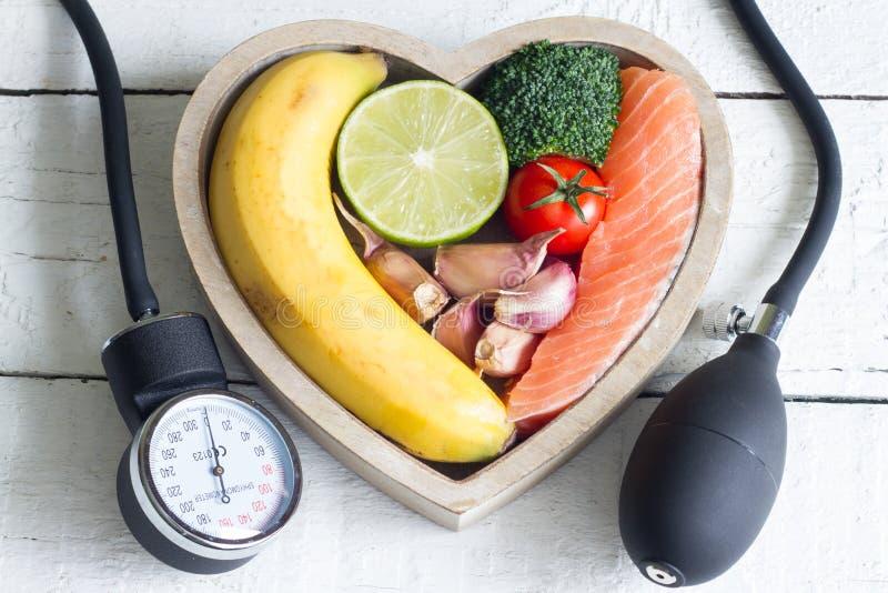 食物和健康心脏饮食概念与血液preasure测量仪在白色板条 免版税库存图片