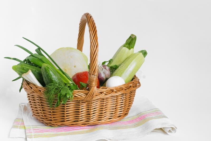 食物和杂货在一个柳条手提篮在一块餐巾在白色背景 消费者篮子 ?? ?? ?? 免版税库存照片