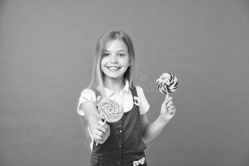 食物和点心 与棒棒糖的女孩微笑在紫罗兰色背景 愉快的孩子用在紫色背景的漩涡焦糖 免版税库存照片