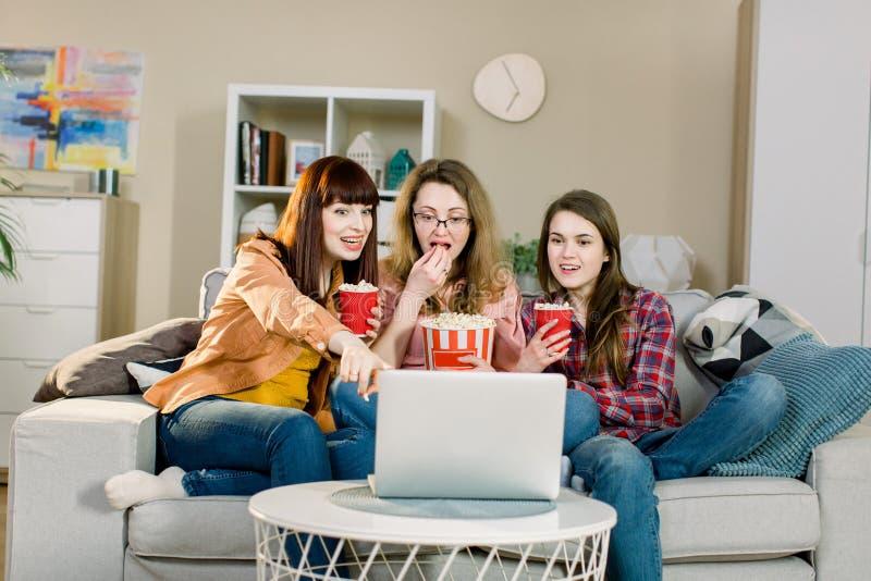 食物和电影 吃玉米花的三个情感俏丽的姐妹,当电影或体育节目一会儿坐 库存图片