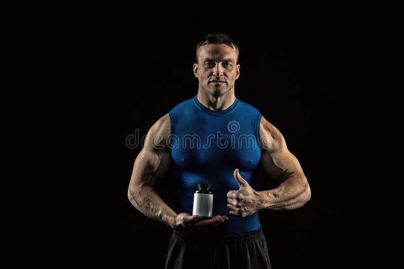 食物和饮食体育和健身的 有维生素瓶展示赞许的运动员 爱好健美者的营养补充 库存照片