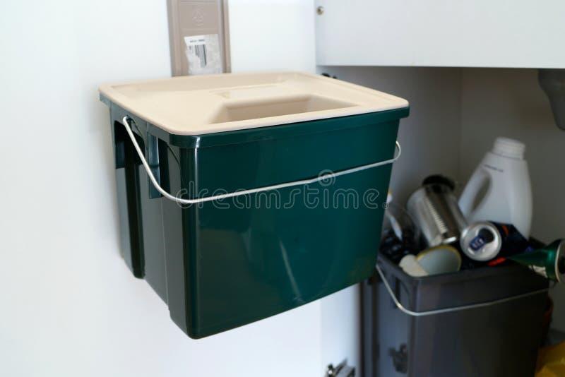 食物垃圾/小块的绿色塑胶容器 在厨房里面的垃圾内阁 回收/堆肥 免版税图库摄影