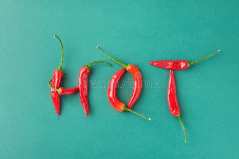 食物字法印刷术 由红色辣辣椒做的词热在绿色背景 墨西哥意大利西班牙希腊烹调 库存图片