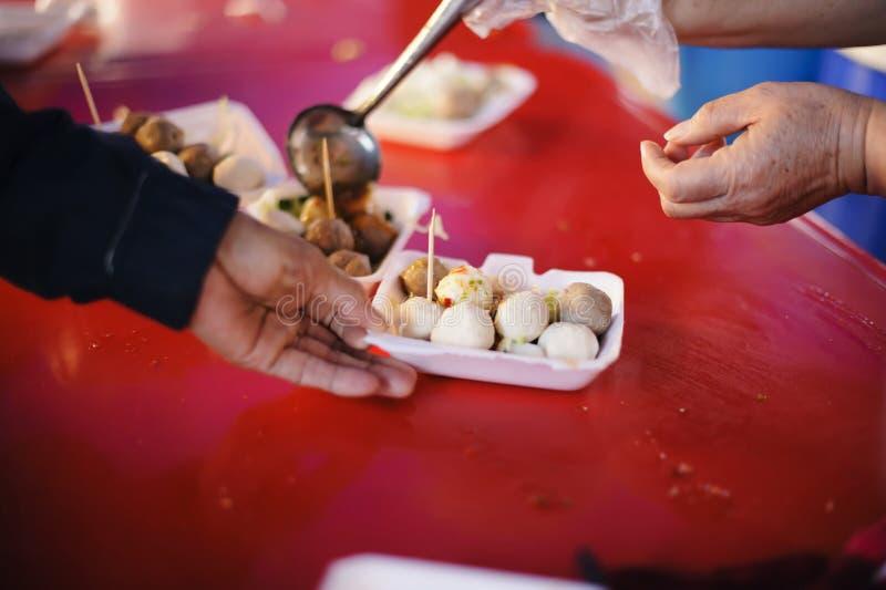 食物捐赠:手饥饿从提供商接受食物 库存照片