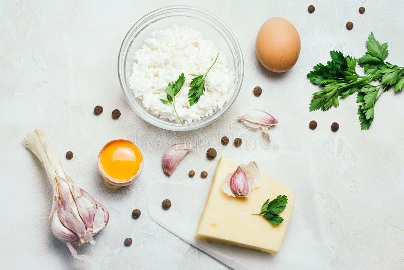 食物有机成份:酸奶干酪 鸡蛋、大蒜和荷兰芹在白色土气具体背景 顶视图,平的位置 库存图片