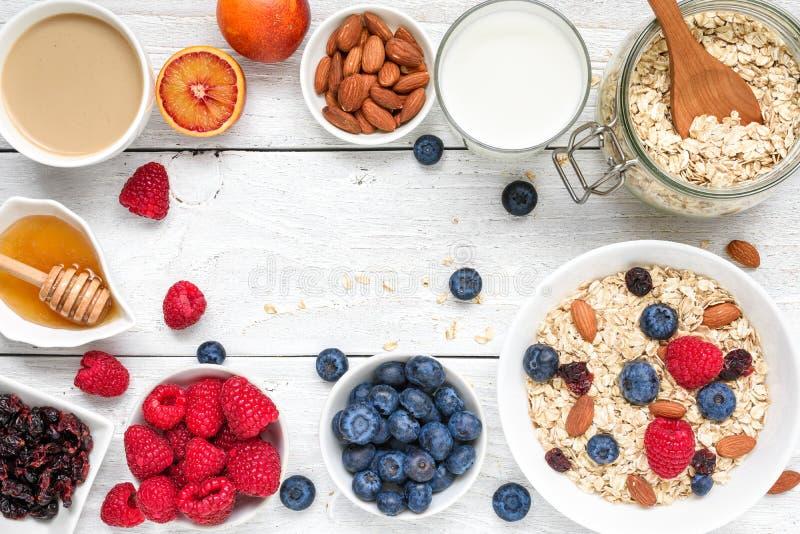 食物框架由早餐成份制成 muesli、果子、莓果,热奶咖啡, nony,牛奶和坚果 健康的食物 免版税库存图片